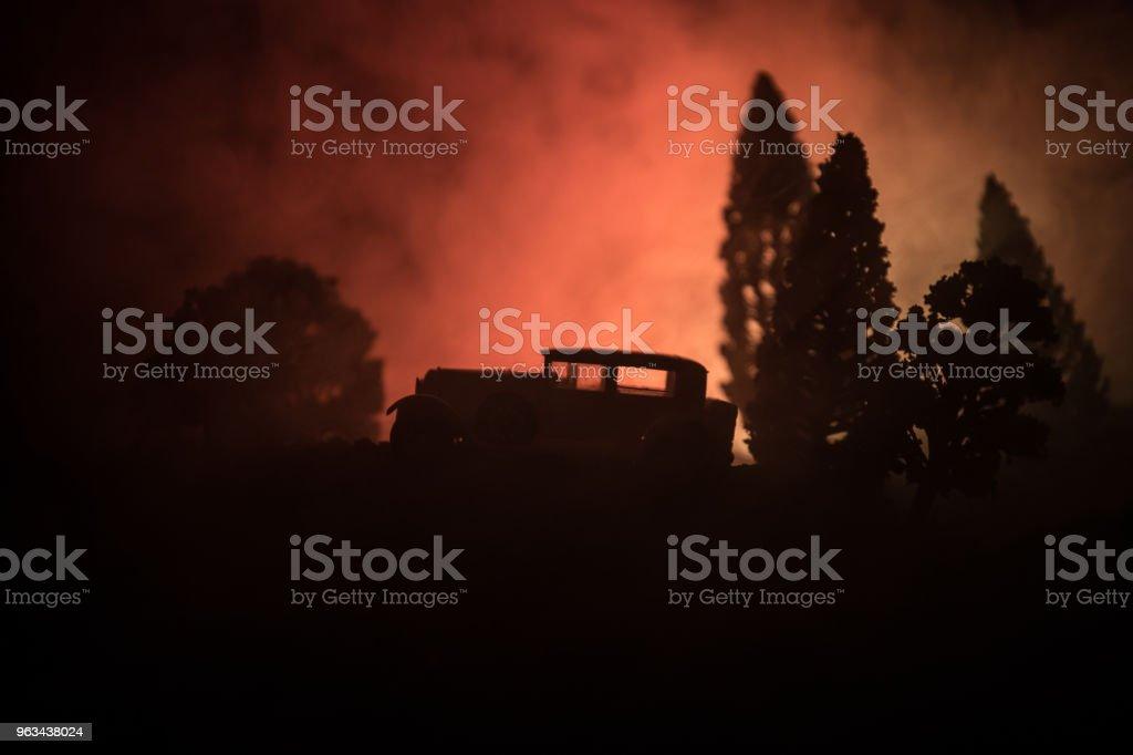 Sylwetka starego zabytkowego samochodu w ciemnym mglistym tle stonowanym z świecącymi światłami w słabym świetle lub sylwetką starego samochodu w ciemnym lesie. - Zbiór zdjęć royalty-free (Bez ludzi)