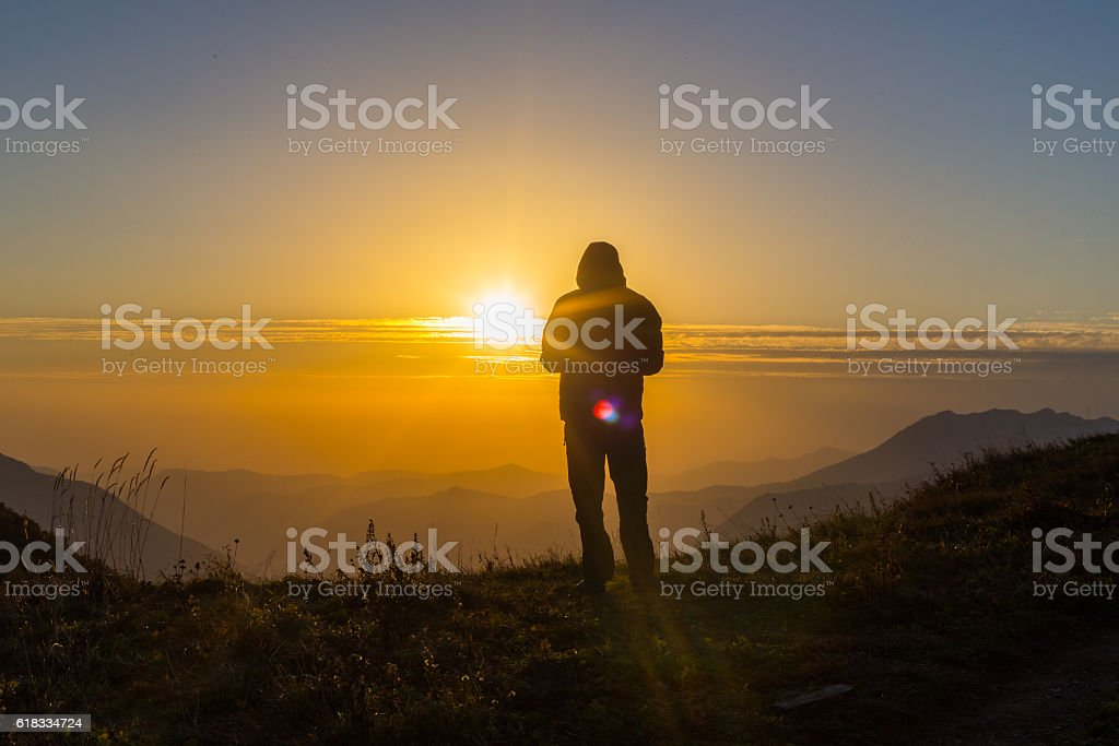 Silhouette of one young man standing at the mountain top stock photo