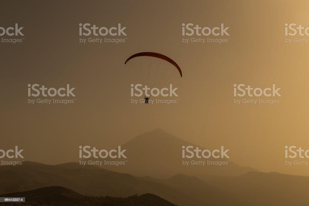 Silhueta de parapente voando no céu da noite com o pôr do sol. - Foto de stock de Acima royalty-free