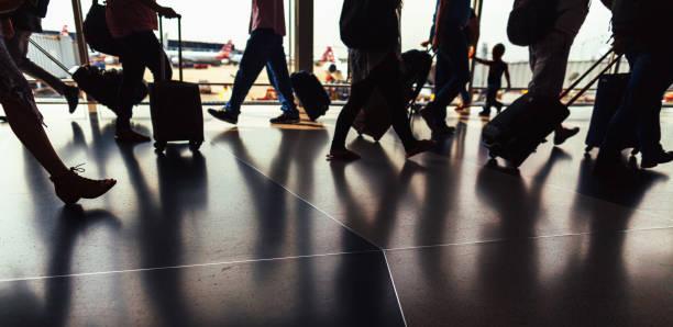 silhouette der passagiere zu fuß durch flughafen flur mit gepäck - kleinkind busy bags stock-fotos und bilder