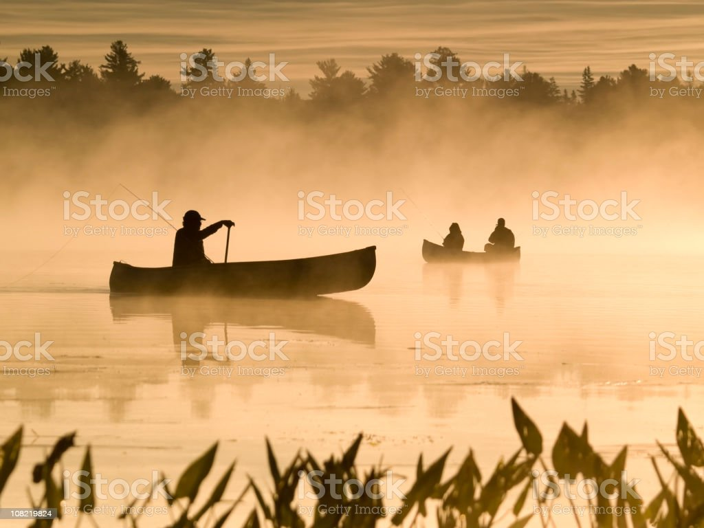 Silhouette of People Canoeing on Lake in Fog royalty-free stock photo