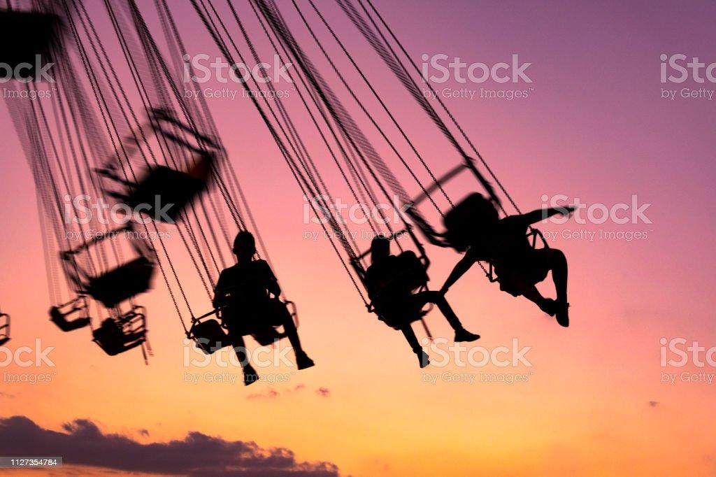 Silhouette der Leute, die Spaß in mechanische Spiel fliegen Stühle in Guatemala, Retalhulehu. Tropischen Nachmittag. - Lizenzfrei Abenteuer Stock-Foto
