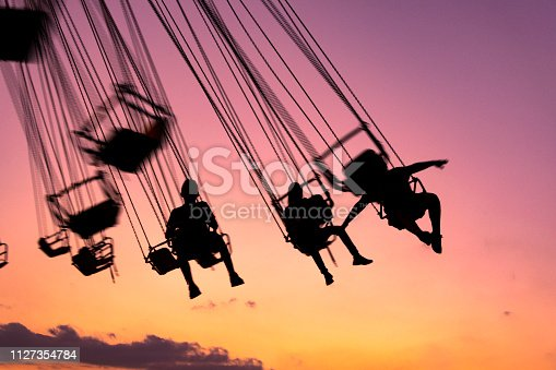 silhouette of people having fun in mechanical game, flying chairs in Guatemala, Retalhulehu.