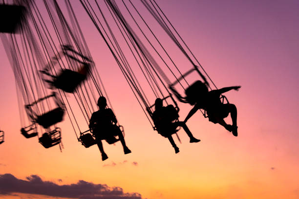 silhouette of people having fun in mechanical game, flying chairs in guatemala, retalhulehu. tropical afternoon. - катание на аттракционах стоковые фото и изображения