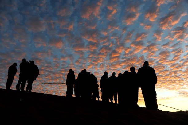 silhouette der menschen vor dem rosa himmel bei sonnenuntergang - trauer abschied tod stock-fotos und bilder