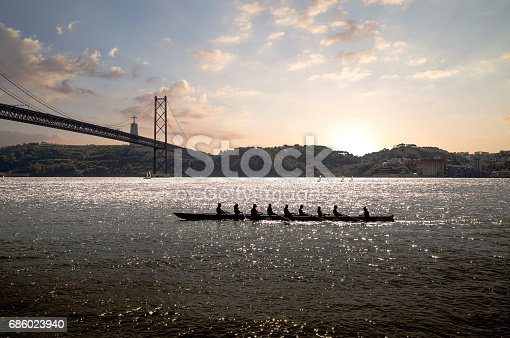 istock silhouette of people on rowing boat on the sea with suspension bridge in the background at sunset. Lisbon, Portugal. 686023940