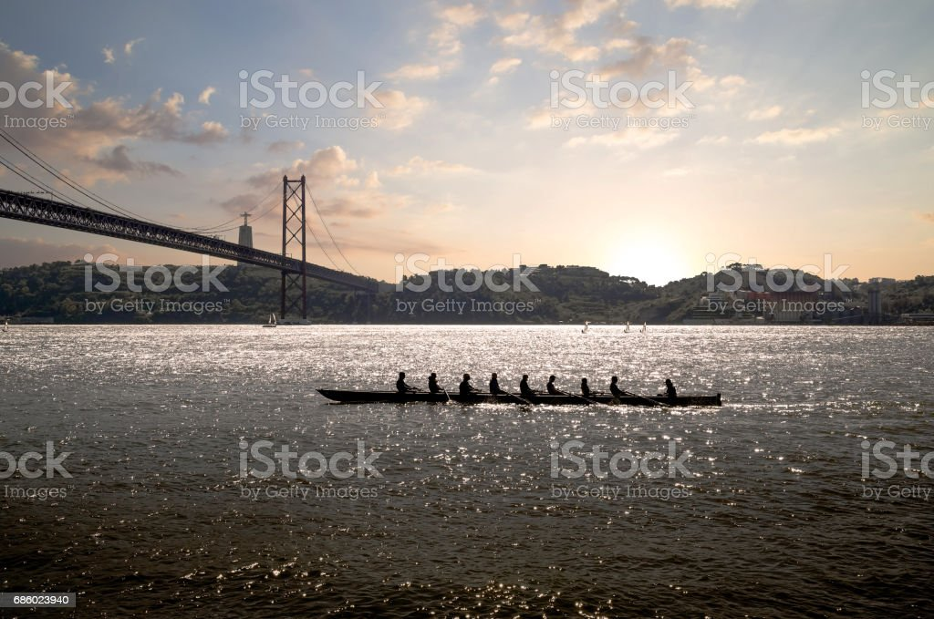 silhouette of people on rowing boat on the sea with suspension bridge in the background at sunset. Lisbon, Portugal. – Foto