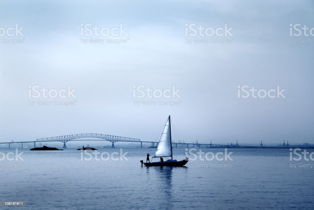 Silhouette of People on Sailboat with Bridge in Background royalty-free stock photo