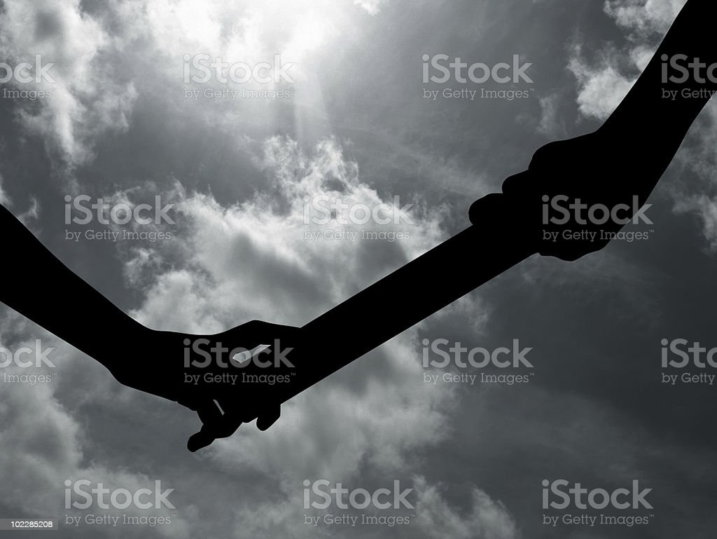 Silhouette of people passing relay baton stock photo