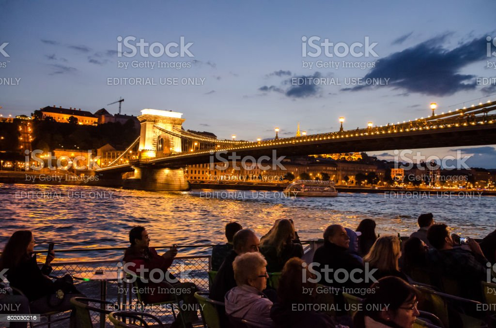 Silhouette of people sitting in a cruise boat on the Danube river and passing under Chain Bridge at summer night stock photo