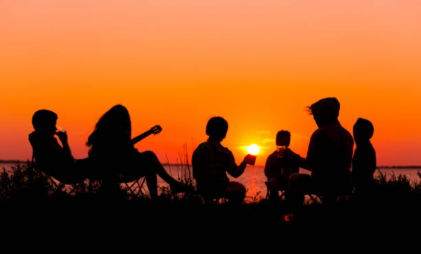 silhouette of people sitting on the beach with campfire at sunse - family gatherings stock pictures, royalty-free photos & images
