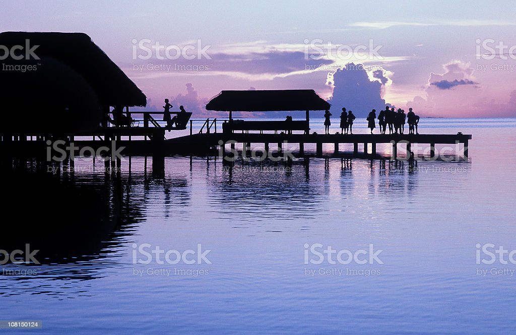 Silhouette of People Standing on Pier Watching Sunset royalty-free stock photo