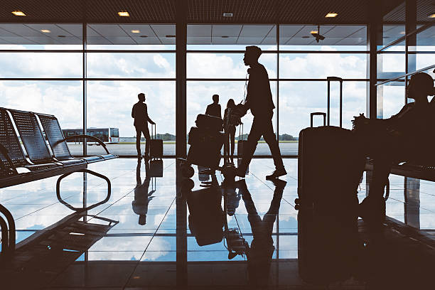 silhouette of people waiting at airport - airport lounge ストックフォトと画像