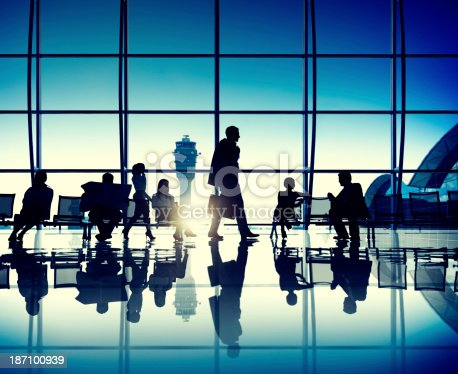 istock Silhouette of people waiting in airport lounge at sunset 187100939