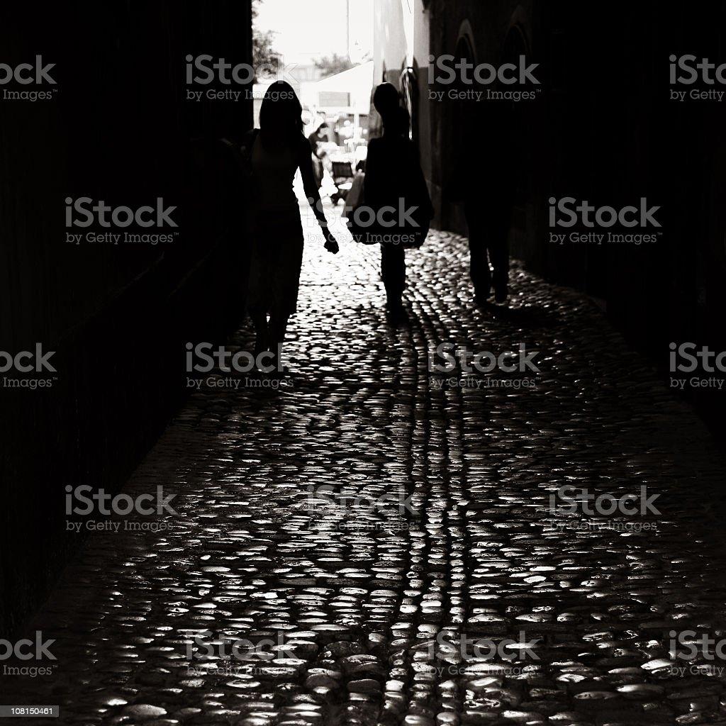 Silhouette of people walking down dark cobblestone alley royalty-free stock photo