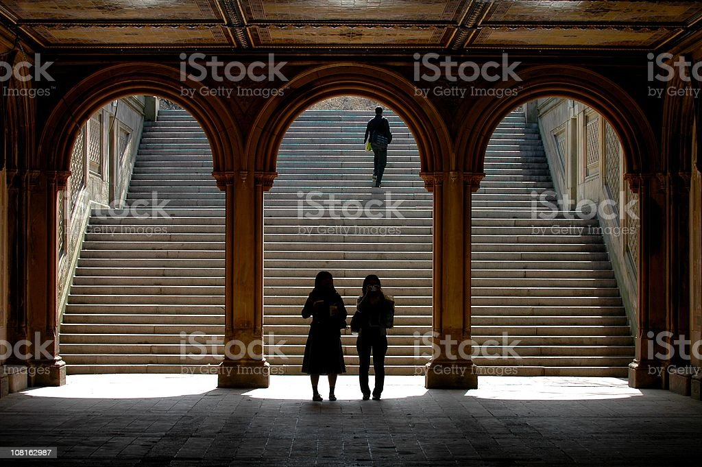Silhouette of People Walking Through Arches in Central Park royalty-free stock photo