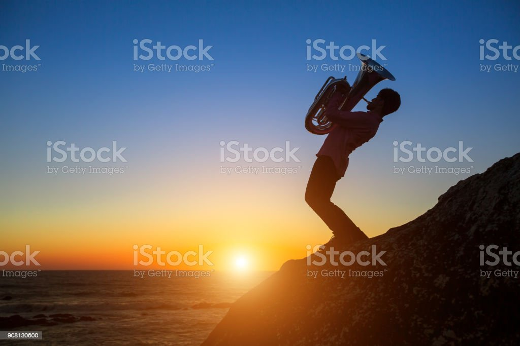 Silhouette of performance musician play Tuba on sea shore at sunset. stock photo