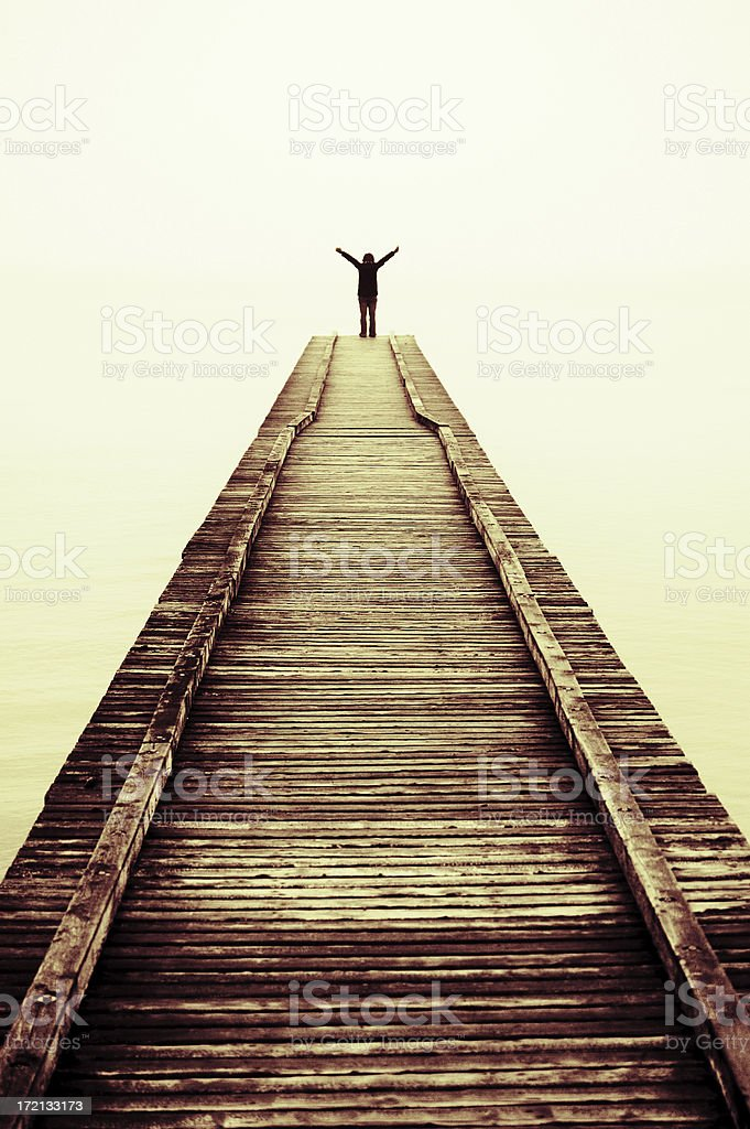 Silhouette of person at the end of a dock arms up stock photo