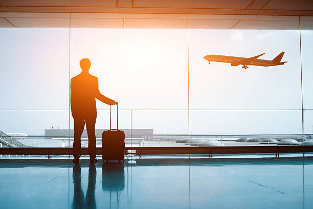 silhouette of person in the airport - airport terminal stock photos and pictures