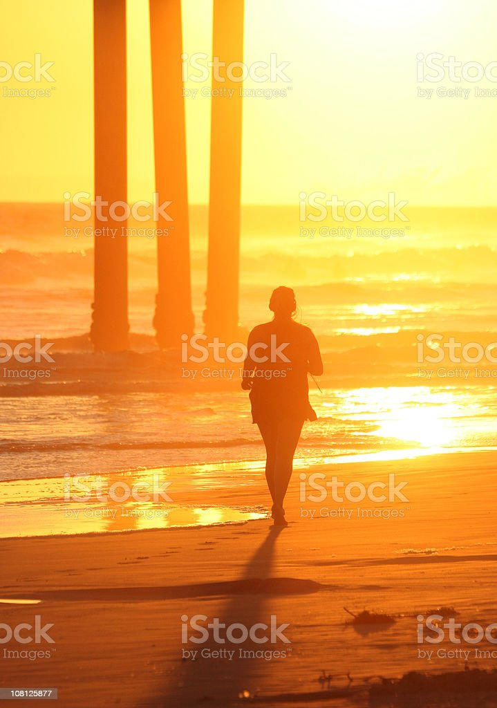 Silhouette of Person Jogging on Beach at Sunset royalty-free stock photo