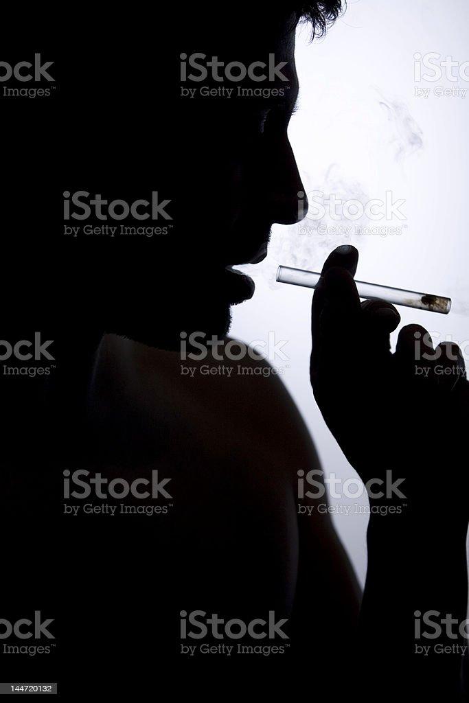 Silhouette of person smoking cigarette stock photo