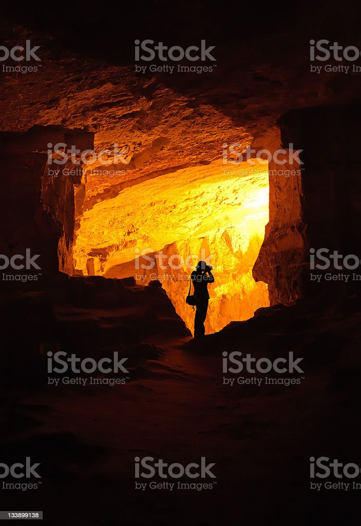 Silhouette of photographer in a cave stock photo