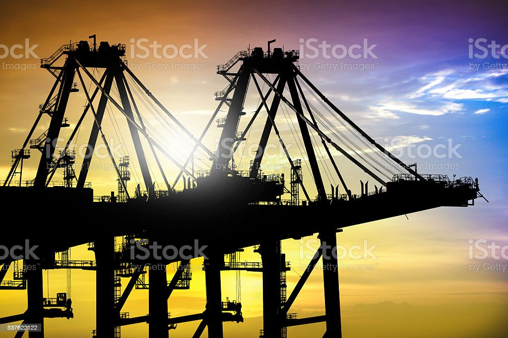 Silhouette of Port cranes working at sunset in sea port. stock photo