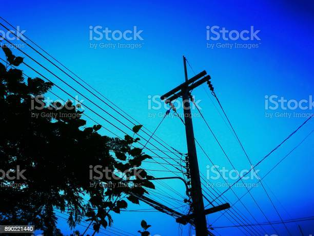 Photo of Silhouette of power lines, telephone transmission wires installed on the same pole.