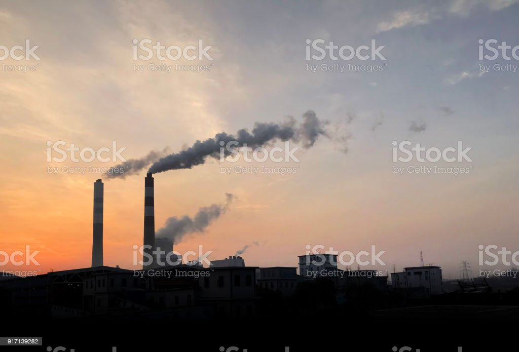 Silhouette of power plant with lots of dark smoke Smoke billows from a smokestack at a power plant, Global Warming 2018 Stock Photo