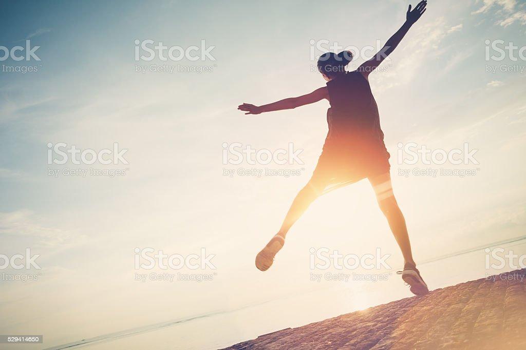 Silhouette of pretty woman jumping near ocean stock photo