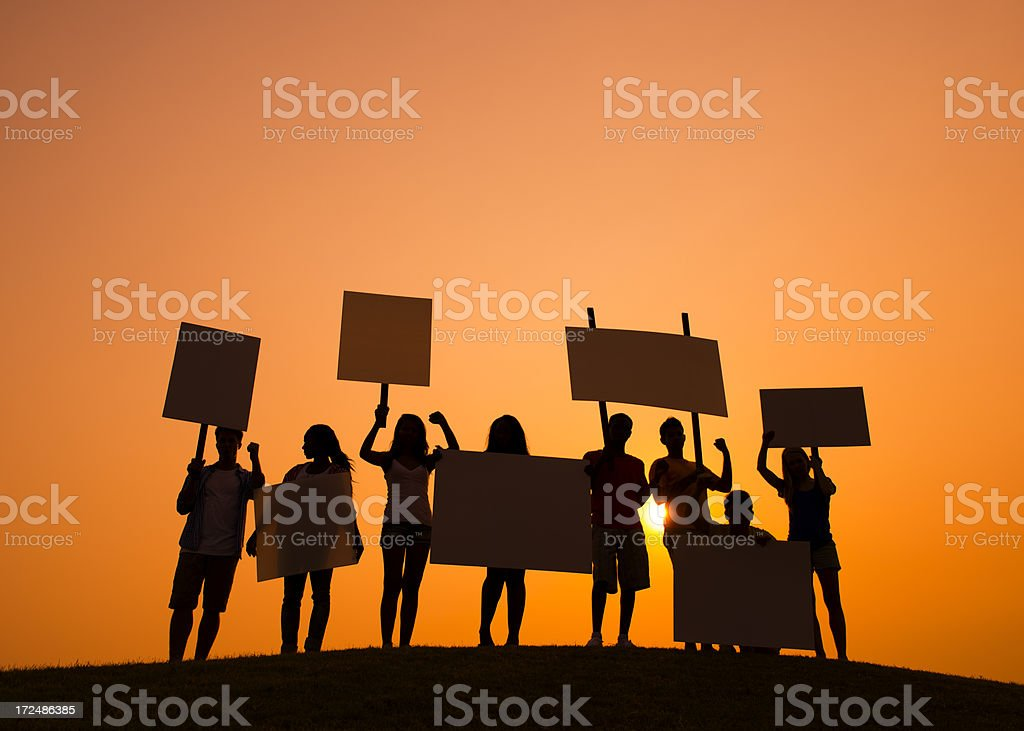 Silhouette of protestors holding signs against an orange sky stock photo