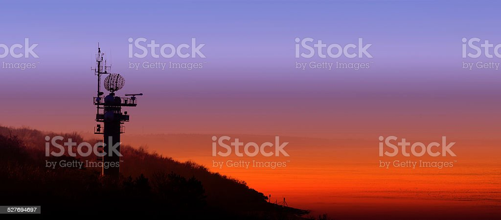 Silhouette of radar station on the Polish coast at sunset. stock photo