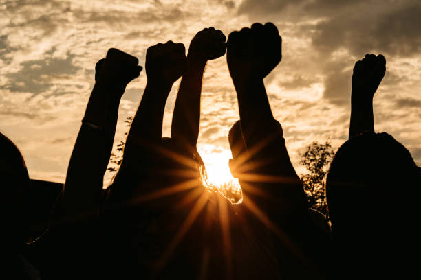 Silhouette of raised fists at sunset stock photo