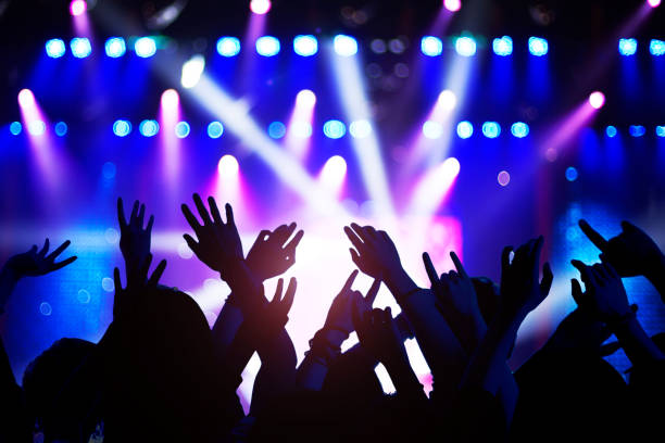 Silhouette of raised hands and arms at concert festival party stock photo
