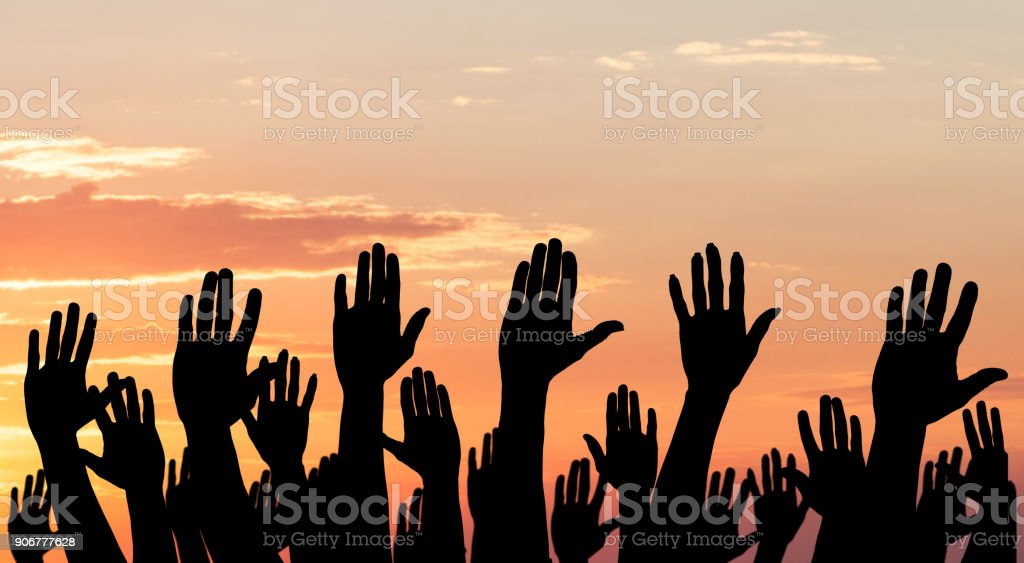 Silhouette Of Raised Hands stock photo