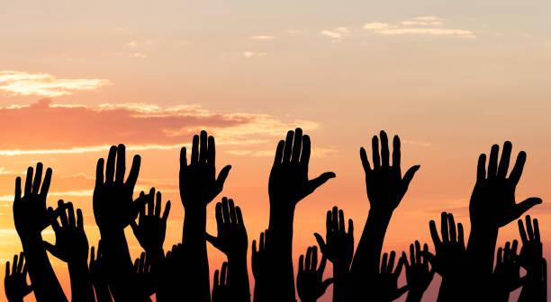 silhouette of raised hands - демократия стоковые фото и изображения