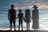 Silhouette Of Refugee Family Standing Near Fence