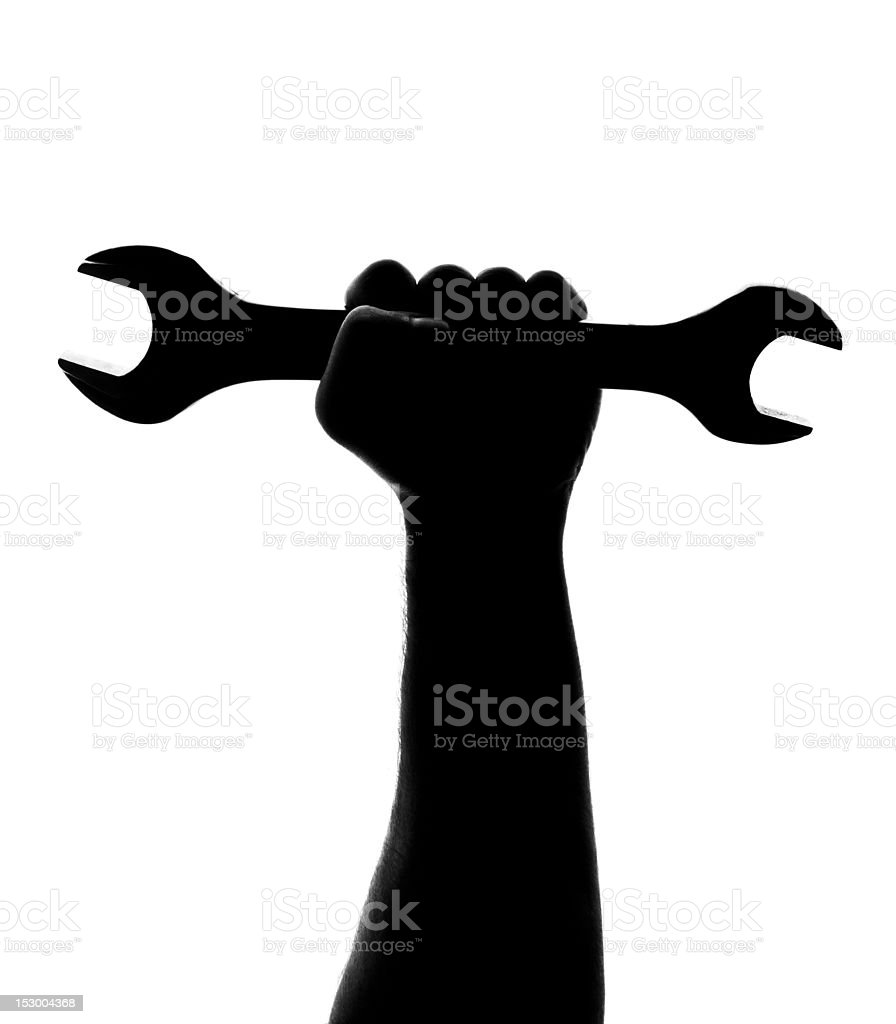 Silhouette of repairman hand with wrench stock photo