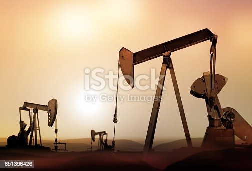 retro oil pumps in deserted district at sunset