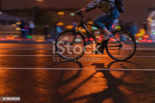istock Silhouette of riding Cyclists on the city roadway, night, abstract, motion blur 929609038