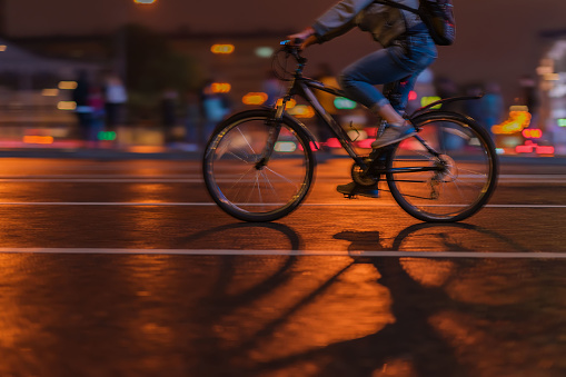 929609038 istock photo Silhouette of riding Cyclists on the city roadway, night, abstract, motion blur 929609038