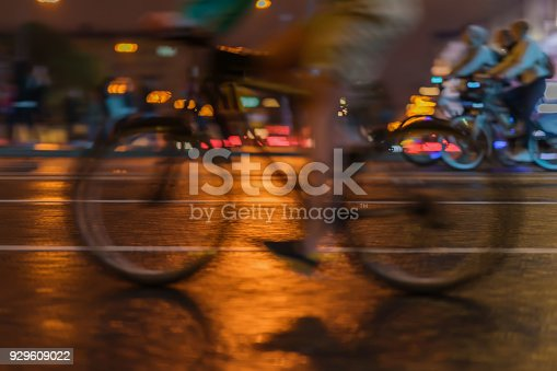 929609038istockphoto Silhouette of riding Cyclists on the city roadway, night light, bokeh, close-up of wheels and legs, abstract, motion blur, for modern background 929609022