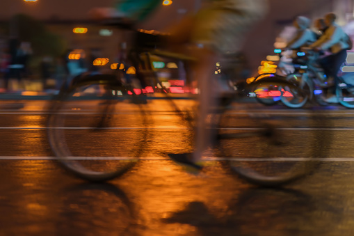 929609038 istock photo Silhouette of riding Cyclists on the city roadway, night light, bokeh, close-up of wheels and legs, abstract, motion blur, for modern background 929609022