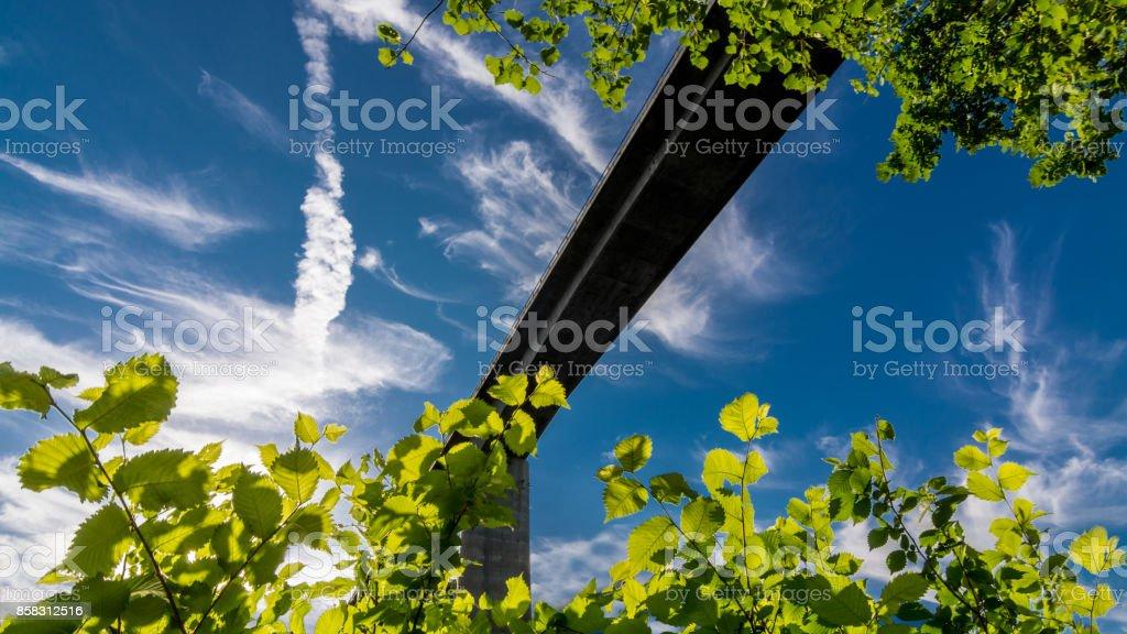 Silhouette of road bridge against blue sky stock photo