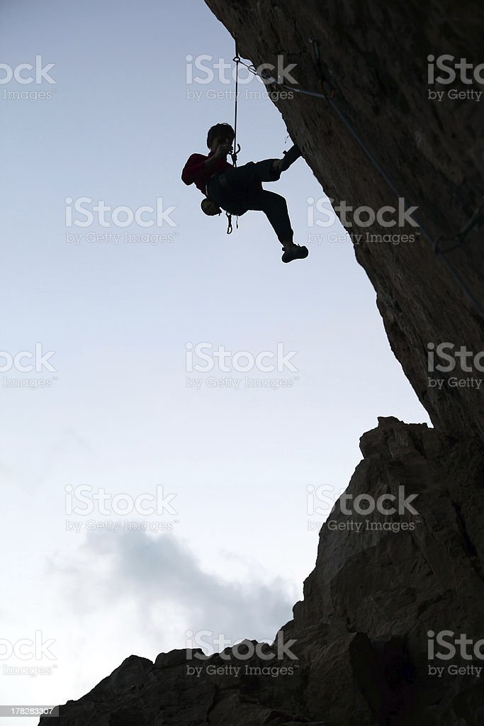 Silhouette of rock climber against sky background stock photo