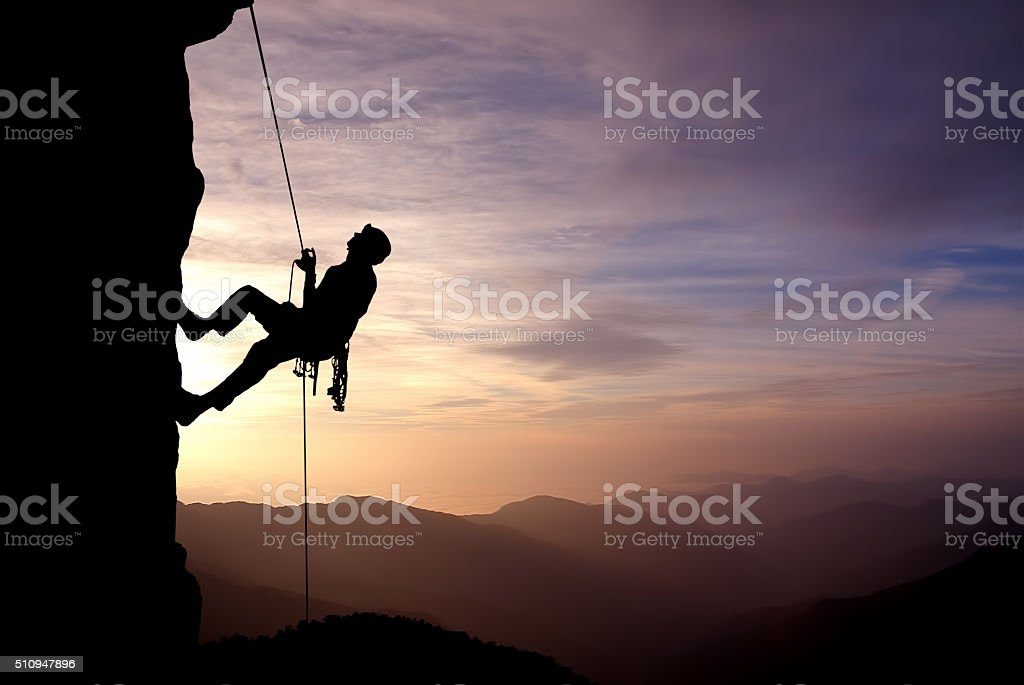 Silhouette of Rock Climber at Sunset stock photo