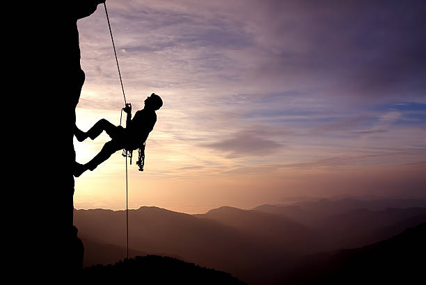 Silhouette of Rock Climber at Sunset Silhouette of a climber on a vertical wall over beautiful sunset persistence stock pictures, royalty-free photos & images