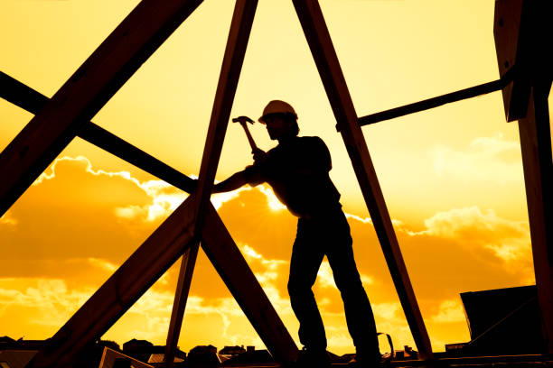 silhouette of roofer worker builder working on roof structure at construction site stock photo