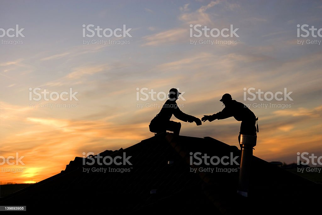 Silhouette of roofers working overtime in the sunset stock photo