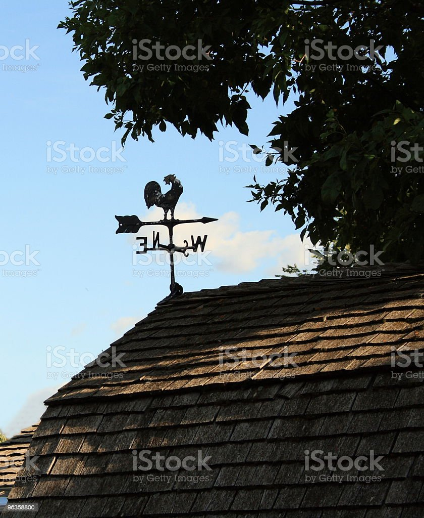 Silhouette of rooster weather vane on shingled roof royalty-free stock photo